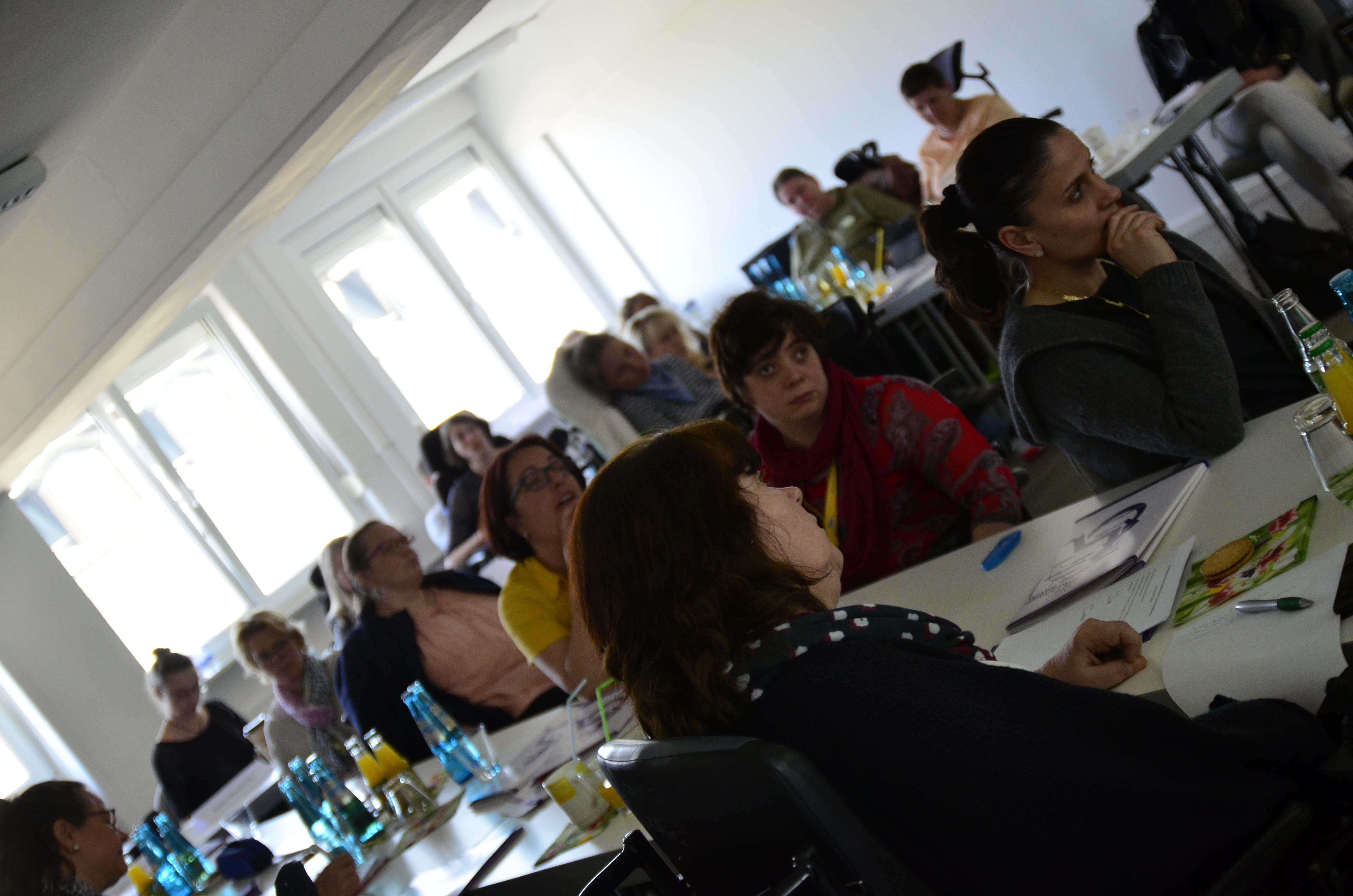Foto vom Plenum im Frühjahr 2018. Frauen mit unterschiedlichen Behinderungen sitzen an langen Tischen. Foto: Anja Kopf und Verena Braun
