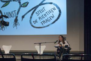 """Katrin Bittl auf einer Bühne mit Mikrofon. Die Präsentation hinter ihr ist nur zum Teil sichtbar: gemalte Wurzeln und Ranken: und die Worte """"KUNST stellt die richtigen Fragen."""