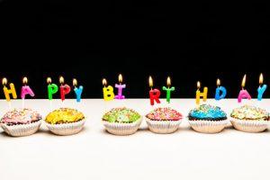 """6 Muffins nebeneinander mit bunter Glasur, darauf brennende Buchstabenkerzen """"Happy Birthday"""""""
