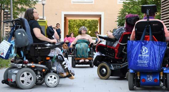 Rollstuhlfahrerinnen stehen beieinander vor der AWO