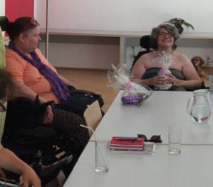 Netzwerkfrau Beri und Netzwerkfrau Karin sitzen am Tisch und freuen sich über ihre noch verpackten Abschiedsgeschenke. Im Hintergrund ist Karins Assistenzhund zu sehen. Auf dem Tisch sind, neben den Geschenken, Getränke und Arbeitsmaterialien.