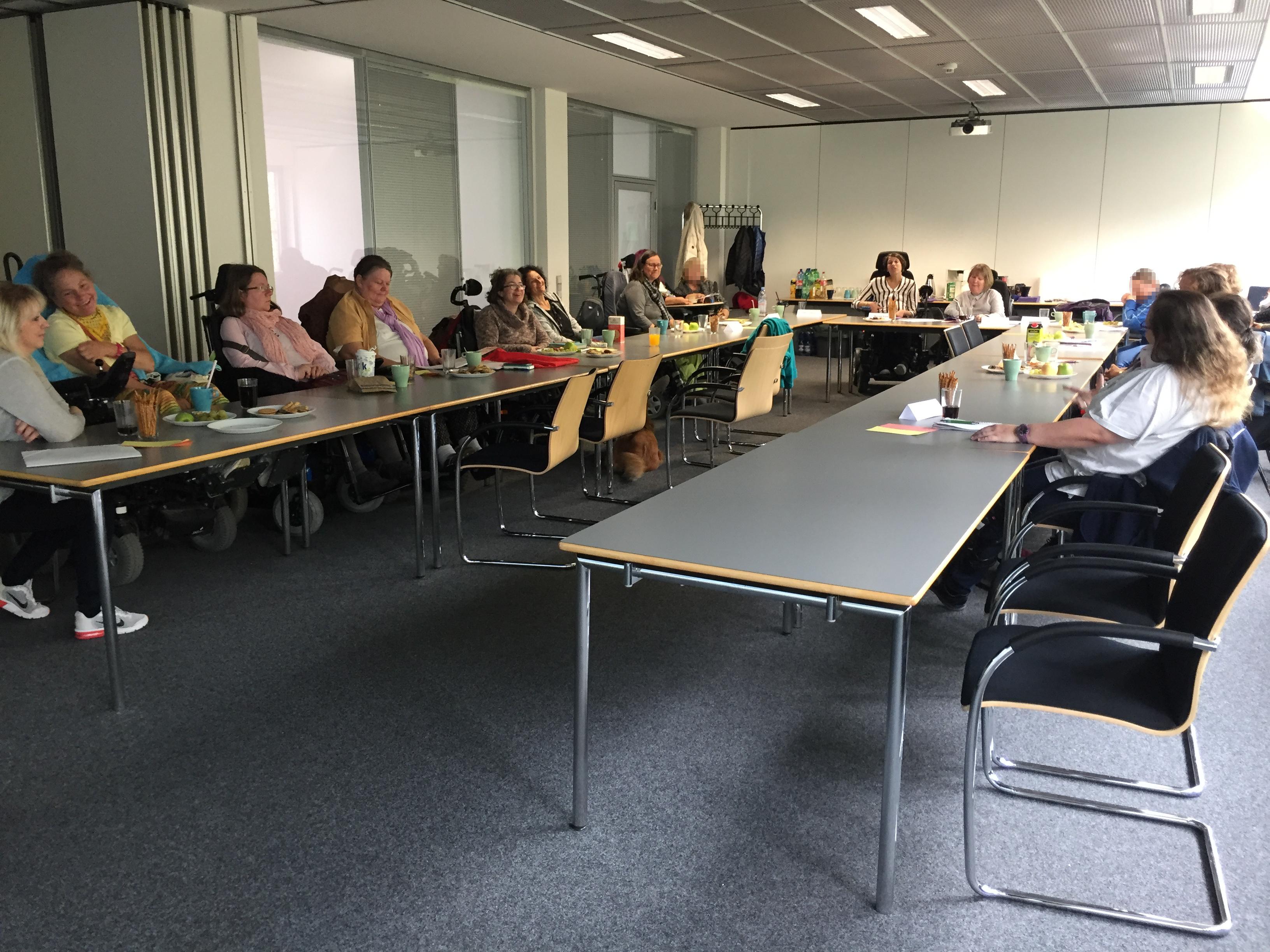 Etwa 15 Frauen der Netzwerkfrauen Bayern sitzen an langen Tischen zusammen beim Plenum