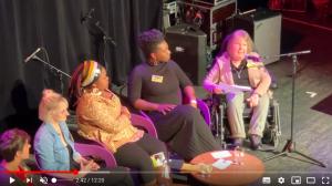 Screenshot aus dem Film zum Weltfrauentag mit Dunja Robin bei ihrem Impulsvortrag und anderen auf der Bühne