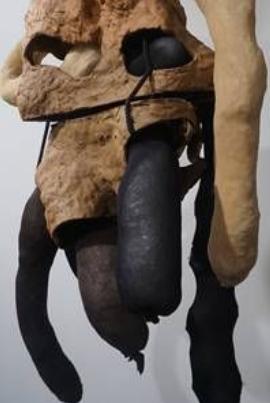 Eine Skulptur in Schwarz und Braun. Zu sehen sind teilweise fellartige Elemente, aus denen und neben denen arm- oder beindicke, gliedmaßenartige Strukturen hängen.